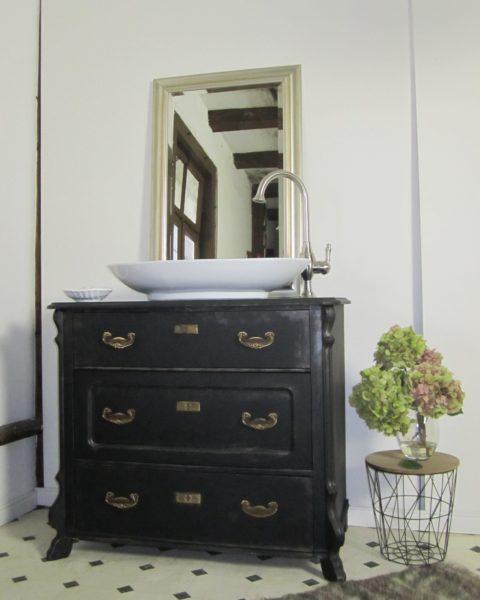 Ein antikes Badmöbel in mattem Schwarz mti einem nostalgisch anmutenden Waschbecken. Ein Bad im Landhausstil.